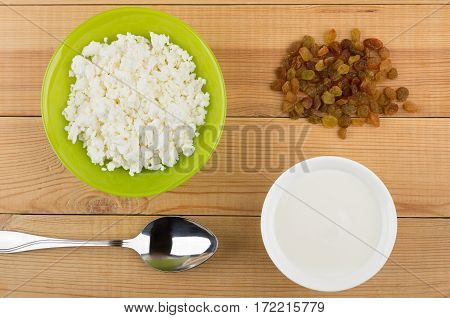 Bowl With Cottage Cheese, Heap Of Raisins, Spoon And Yogurt
