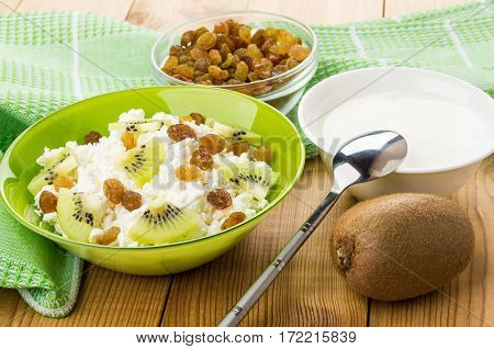 Bowl With Cottage Cheese, Raisins And Slices Of Kiwi On Table