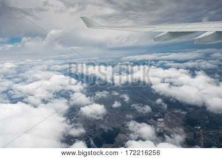 Sydney, Australia - Oct 29, 2016: Flying in between the clouds, moments after plane takes off from Sydney Kingsford-Smith International Airport. Sydney suburbia below.