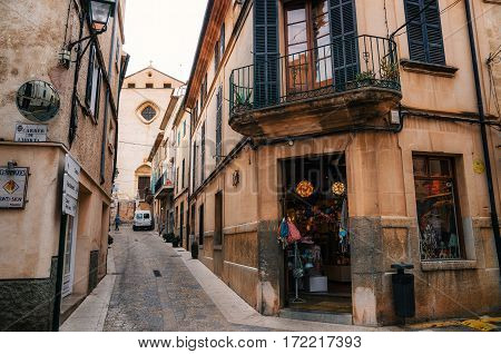 Pollensa Mallorca Spain - May 24 2015: Narrow winding streets in historical town part of Pollensa with traditional stone houses souvenir shops and medieval church in Majorca island