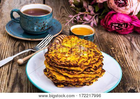 Vegetarian vegetable fritters with honey, tea in vintage cup. Studio Photo