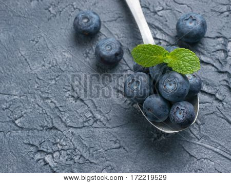 Freshly picked blueberries in spoon closeup. Ripe and juicy fresh blueberry with green mint leaves on textured concrete background. Bilberry on dark background with copyspace. Top view or flat lay