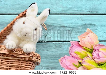 Toy rabbit in the basket and flowers on wooden blue pastel background.