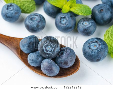 Freshly picked blueberries in wooden spoon closeup. Ripe and juicy fresh blueberries with green mint leaves on white background. Bilberry antioxidant. Healthy eating concept