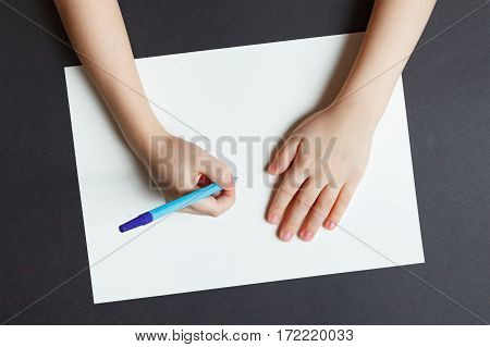 Hand of a child writing on white paper