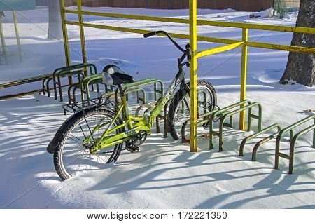 MOSCOW RUSSIA - JANUARY 11 2017: Lonely bicycle left on all winter at the bicycle parking. Moscow near the entrance to the main building of Moscow State University.