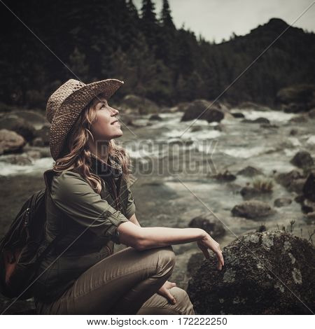 Beautiful woman hiker near wild mountain river