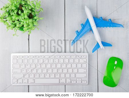 Plane, Computer Keyboard And Mouse On White Wooden Table