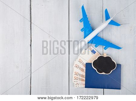 Plane, Passport, Blackboard And Paper Money On White Wooden Table