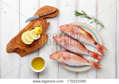 Fresh red mullet fish cooking with oil, herbs and lemon on white wooden background