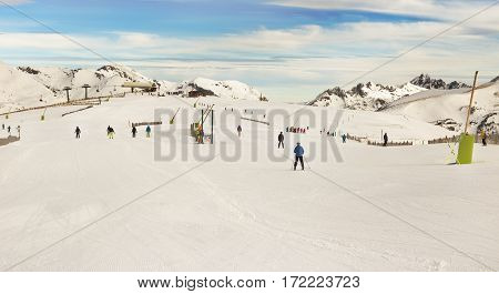 PYRENEES ANDORRA - FEBRUARY 10 2017: Unknown skiers on an alpine skiing in the Pyrenees Andorra. A view of ski lifts tops of mountains in snow and ski slopes of the route