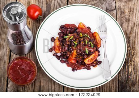 Red beans, tomatoes, ketchup, onion and spices on the white plate. Studio Photo