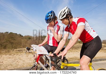Two lost cyclists looking for a map for directions, standing over their bicycles