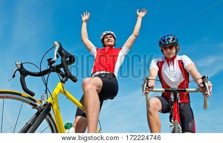 Cyclist raising his arms after crossing the finish line, inches in front of his competitor: Photo finish