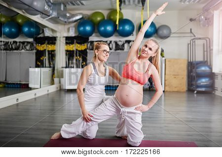 Confident Pregnant Woman Training Yoga With Personal Coach