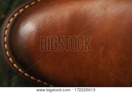 Background texture of leather. Leather Shoe closeup with stitched sole. Fashionable casual wear