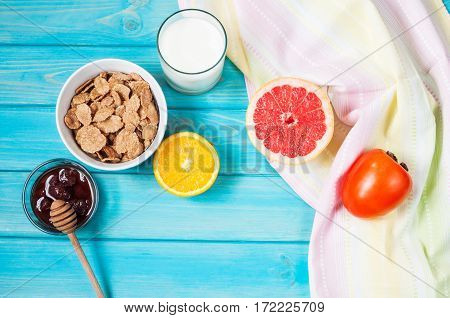 Bowl of healthy corn flakes breakfast cereal milk and fruits on blue wood table. Top view