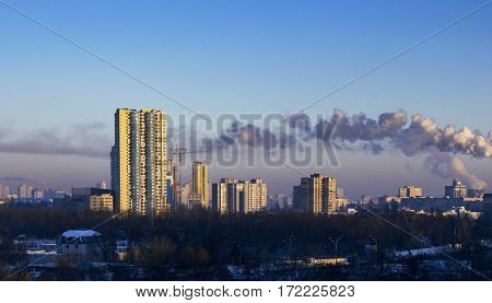 Skycrapers early in the morning with yellow light on the walls. Townscape with smoke emissions. Residantial areas in Kiev