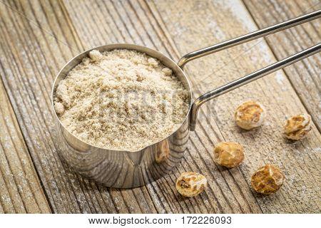 organic tiger nut powder in a metal measuring scoop against grunge wood background