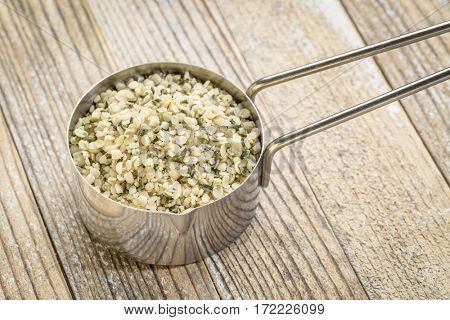 hemp seed hearts in a metal measuring scoop against grunge wood background