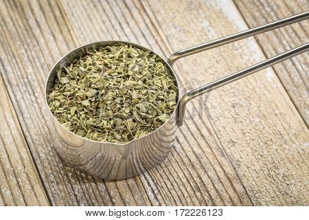 oregano leaf in a metal measuring scoop against grunge wood background