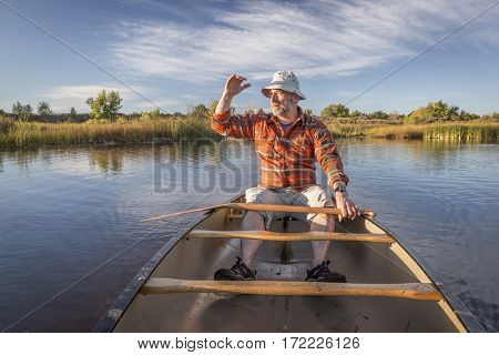 senior male enjoying evening sun on lake in a canoe, Riverbend Ponds Natural Area, Fort Collins, Colorado
