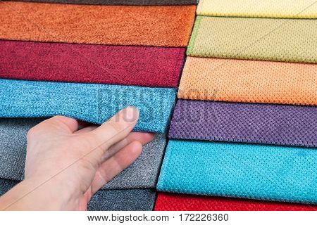 Woman chooses samples of colored fabric on table close up