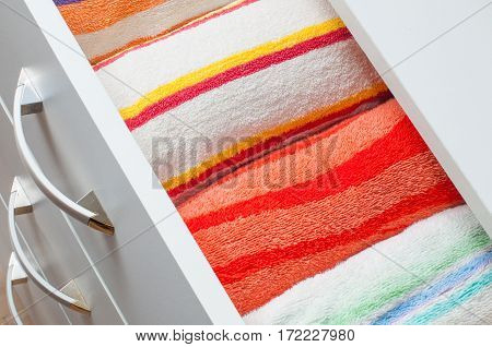 Striped colorful towels in the drawer chest