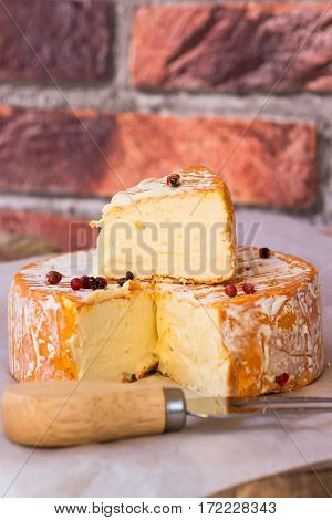 Soft cheese with cut off slice creamy texture orange rind with mold French German Alps red pepper corns close up brick wall background