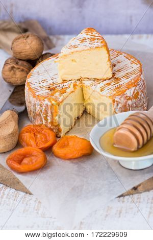 Soft cheese with cut off slice creamy texture orange rind with mold French German Alps honey dipper walnuts dried apricots knife top view rustic kitchen interior