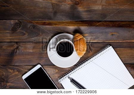 White Cup Of Coffee And Mobile Phone And Lying Next To Notebook With Pen, Croissant