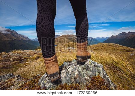 Detail Of Woman's Legs In Trekking Shoes With Mountain Range Background