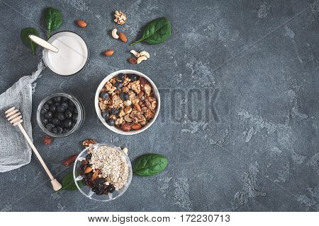 Healthy breakfast with muesli yogurt blueberry nuts on grunge background. Flat lay top view