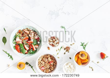 Breakfast with muesli strawberry salad fresh fruit nuts on white background. Healthy food concept. Flat lay top view