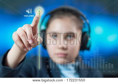 girl with headphones adjust the volume of music on a transparent screen