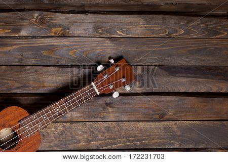 Musical string instrument ukulele on wooden background