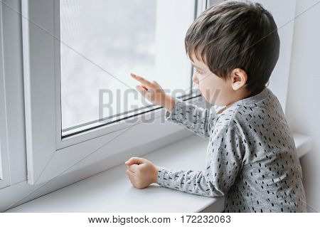 Little sick boy in gray pajamas looking through window.