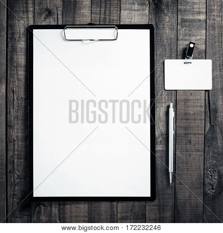 Blank letterhead badge and pen. Blank ID template on wooden table background. Mock up for placing your design. Top view.