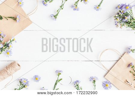Flowers composition. Gifts and wildflowers on wooden white background. Flat lay top view
