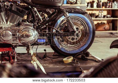 Focus on wheel of motorcycle situating near repair tools in garage