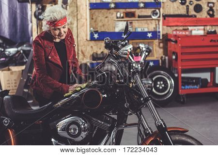 Pretty outgoing female retiree cleaning her motorcycle in comfortable garage
