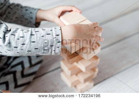 child boy playing with block toys. wooden constructor.
