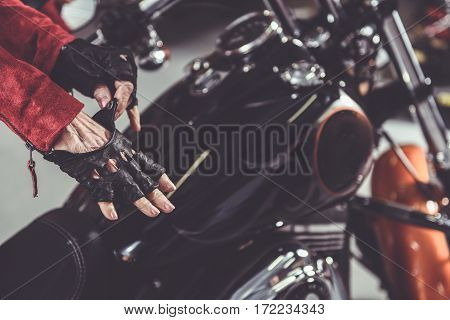 Old female woman putting on leather gloves while standing near bike in mechanic shop. Close up of her hands