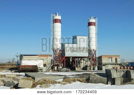 Exterior view of a cement factory. Concrete mixing silo, site construction facilities.
