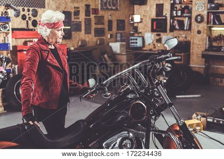 Calm retiree standing near her bike in wide cozy motor vehicle storage building