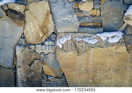 The fence of the different structure of large stones background
