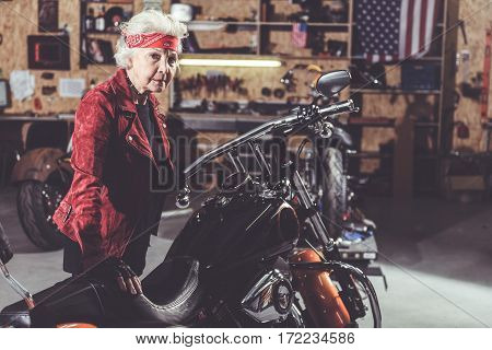 Thoughtful grandmother leaning her hand on bike in wide garage