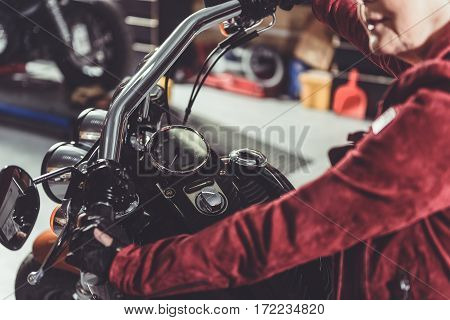 Focus on arm of retiree situating on bike while she driving from mechanic shop