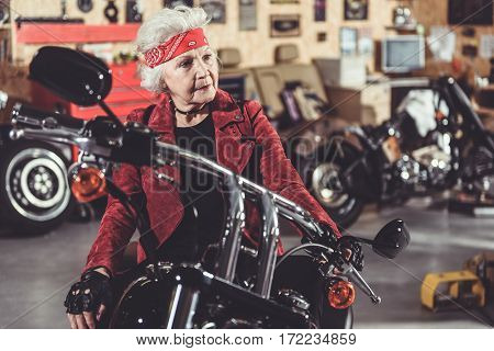 Thoughtful female pensioner sitting on motorcycle in wide comfortable garage