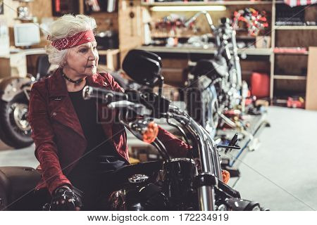Outgoing old woman situating on bike in cozy mechanic shop